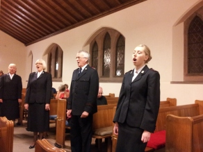 Three members of the International Staff Songsters singing in the aisles of Teviot Church